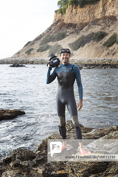 Hispanic diver wearing wetsuit on beach