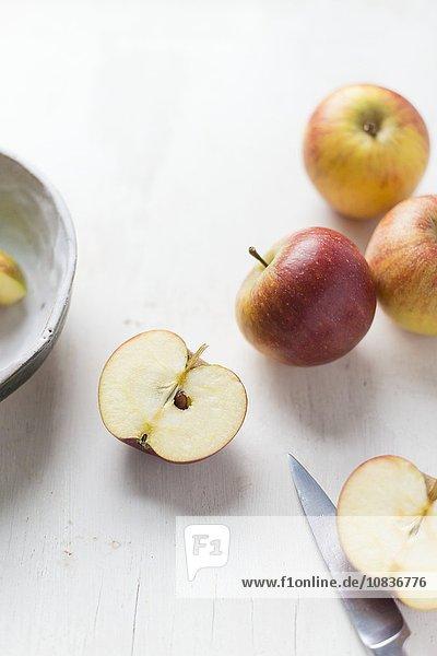 Äpfel auf weissem Untergrund mit halbiertem Apfel und Messer
