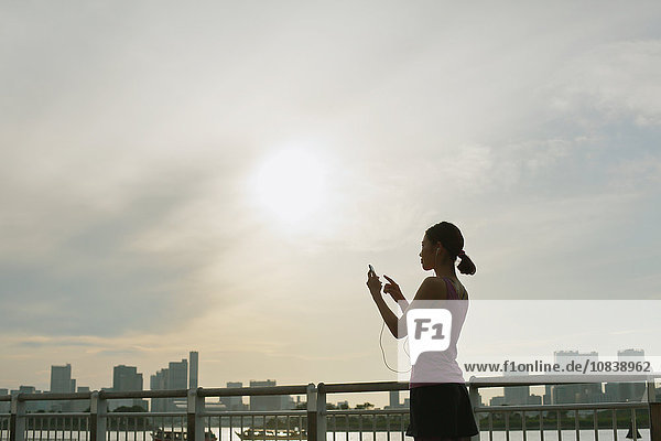 Young Japanese with smartphone during her run downtown Tokyo