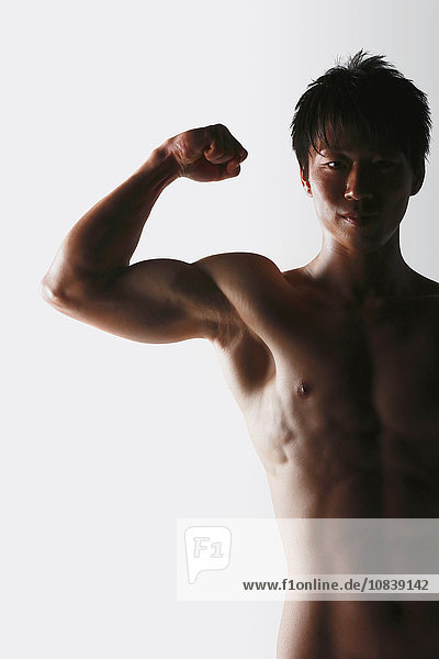 Japanese male athlete showing off muscles