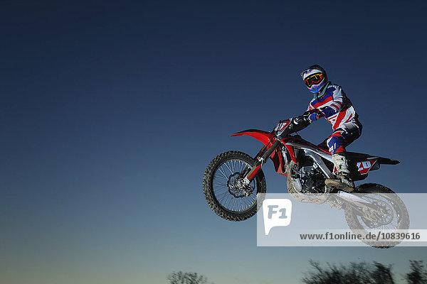 Motocross biker jumping over dirt track