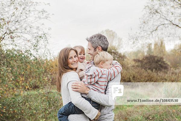 Lächelnde Familienumarmung im Herbstpark
