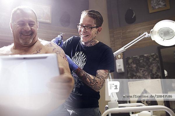 Lächelnder Mann mit digitalem Tablett und Schulter-Tattoo