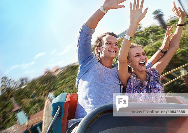 Exhilarated young couple riding amusement park ride