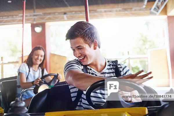 Lächelnder junger Mann mit Autoscooter im Vergnügungspark