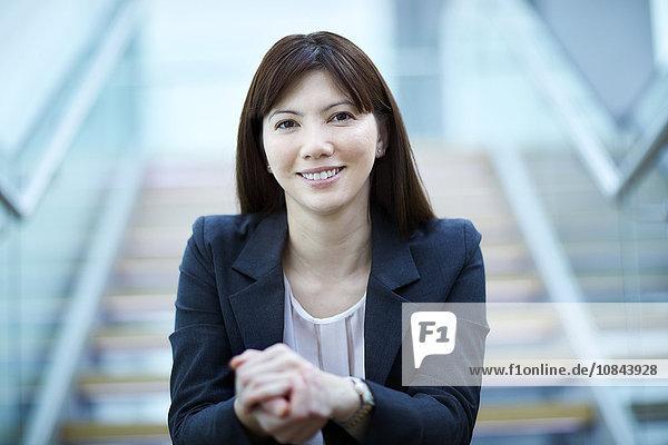 Portrait selbstbewusste Geschäftsfrau auf der Treppe sitzend