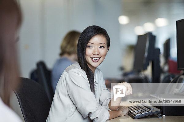 Lächelnde Geschäftsfrau im Gespräch mit Amtskollegin