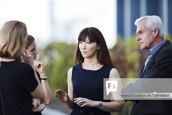 Businesswoman gesturing and talking to colleagues