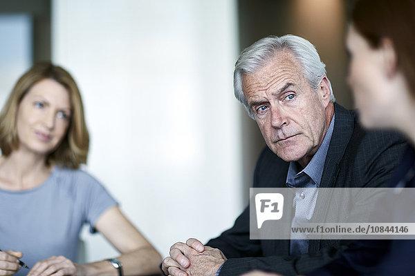 Serious Senior Geschäftsmann hören Geschäftsfrau in der Sitzung