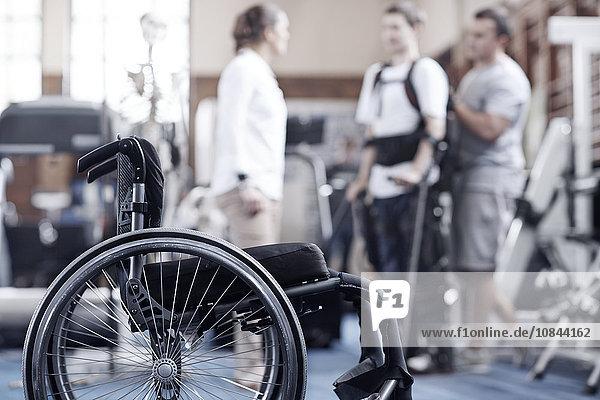 Mann in Physiotherapie mit Rollstuhl im Vordergrund
