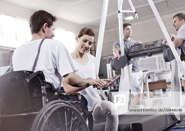 Physiotherapeutin zeigt dem Menschen im Rollstuhl Tablet PC