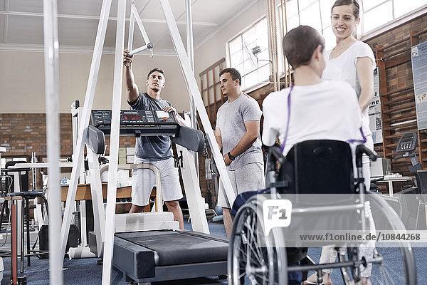 Physiotherapeuten bereiten Laufband für Menschen im Rollstuhl vor