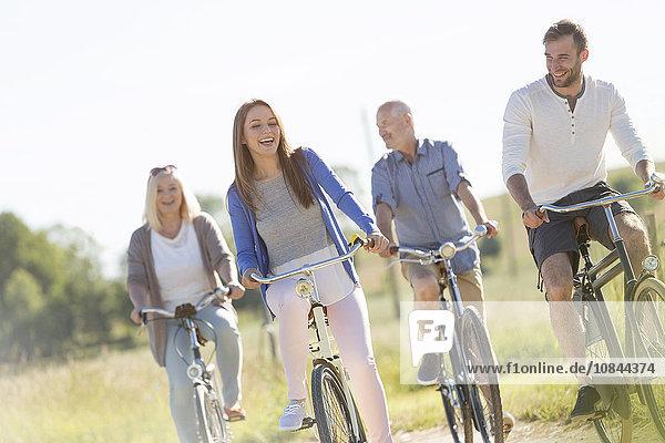 Fröhliches Familienradfahren im sonnigen Feld