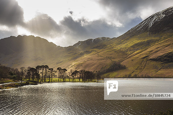 Shafts of light break through clouds to illuminate the fells in winter  Buttermere  Lake District National Park  Cumbria  England  United Kingdom  Europe