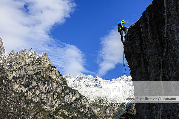 Climber on steep rock face in the background blue sky and snowy peaks of the Alps  Masino Valley  Valtellina  Lombardy  Italy  Europe