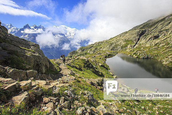 Low clouds and mist around Grandes Jorasses and Mont Blanc while hikers proceed on Lac De Cheserys  Haute Savoie  French Alps  France  Europe