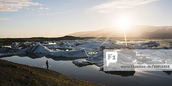Tourist at Jokulsarlon Glacier Lagoon at sunset  South East Iceland  Iceland  Polar Regions