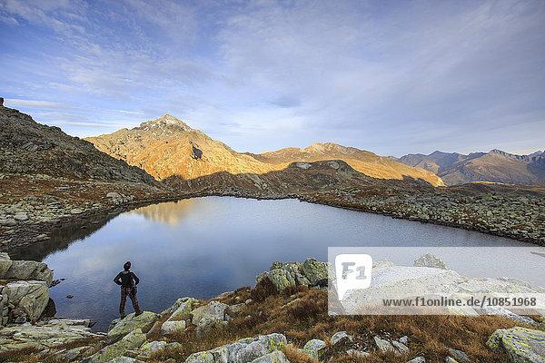 Hiker admires Lake Bergsee at sunrise  Chiavenna Valle  Spluga Valley  Switzerland  Europe