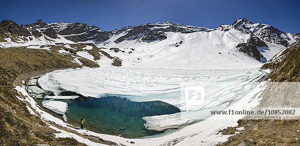 Photographer at Laj dal Teo where snow begins to melt due to spring thaw  Poschiavo Valley  Switzerland  Europe
