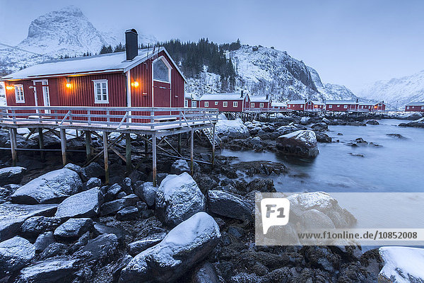 Typical fishermen houses called rorbu in the snowy landscape at dusk  Nusfjord  Nordland County  Lofoten Islands  Norway  Scandinavia  Europe