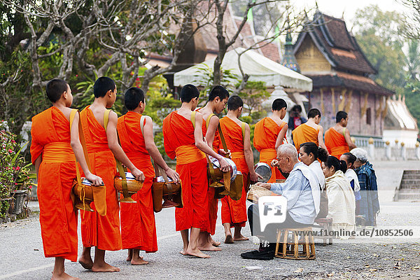 Monks recieving morning alms and Xieng Thong Monastery in the background  Luang Prabang  Laos  Indochina  Southeast Asia  Asia