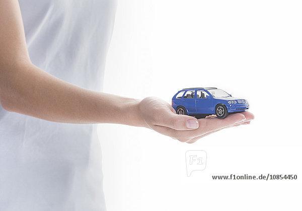 Blaues Modellauto auf Frauenhand