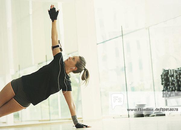 Frau balanciert in der Seitendiele im Fitnessstudio
