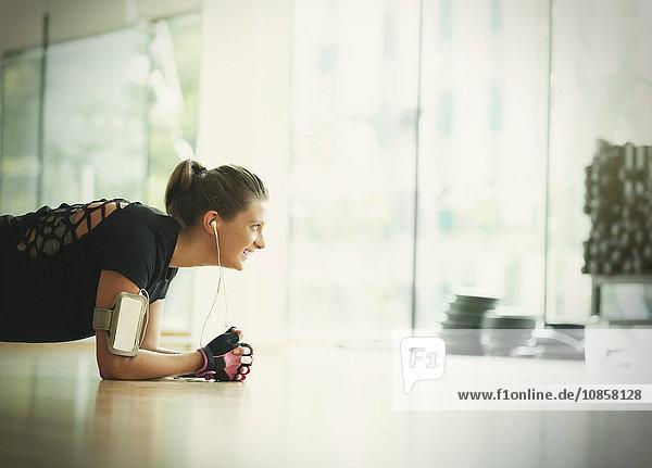 Lächelnde Frau in Brettchenstellung auf dem Boden des Fitnessstudios