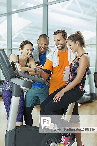 Freunde mit dem Handy am Heimtrainer im Fitnessstudio