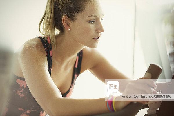 Fokussierte Frau mit Heimtrainer im Fitnessstudio