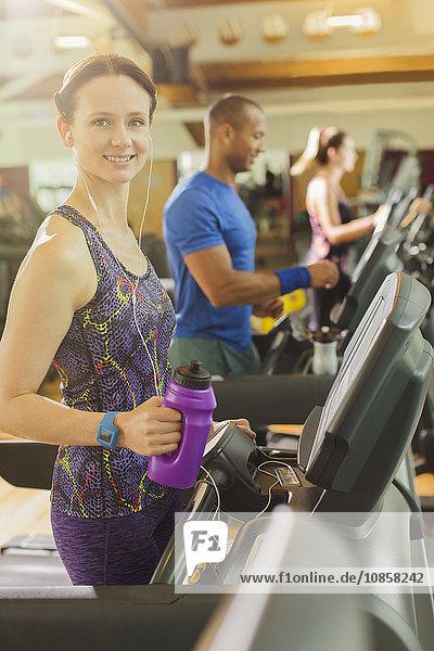 Portrait lächelnde Frau mit Wasserflasche auf dem Laufband im Fitnessstudio