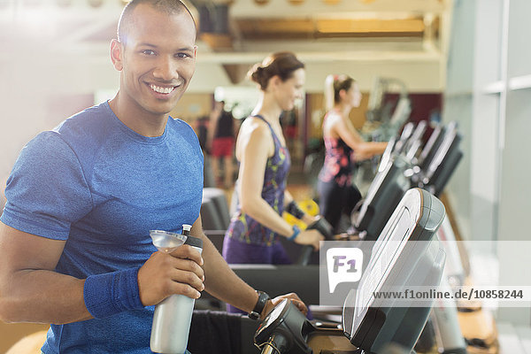Portrait smiling man with water bottle on treadmill at gym