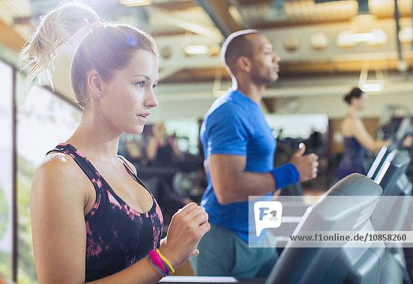 Fokussierte Frau auf dem Laufband im Fitnessstudio