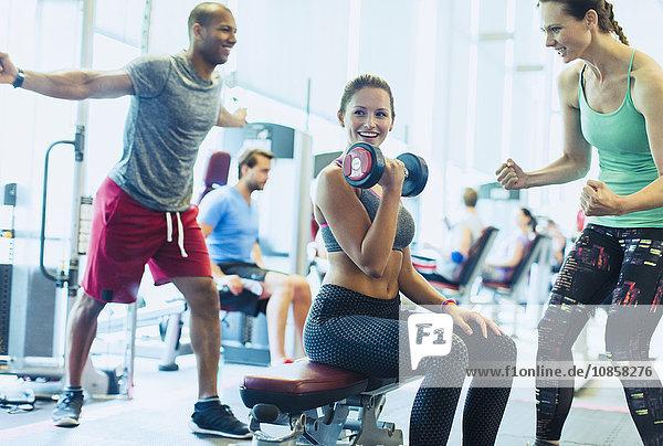 Frau jubelt einem Freund zu  der Hantel-Bizeps-Locken im Fitnessstudio macht.