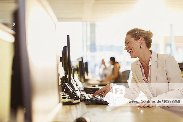 Lachende Geschäftsfrau bei der Arbeit am Computer im Büro