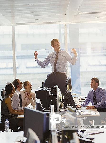 Überschwänglicher Geschäftsmann feiert auf Schreibtischen im Büro