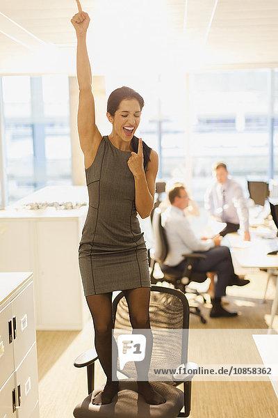 Überschwängliche Geschäftsfrau feiert auf Bürostuhl