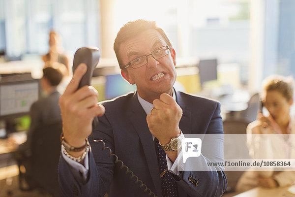 Wütender Geschäftsmann gestikuliert mit der Faust am Telefon im Büro