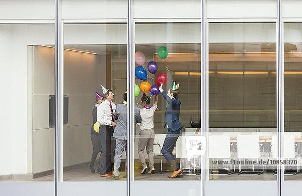 Verspielte Geschäftsleute in Partyhüten feiern mit Luftballons im Konferenzraum