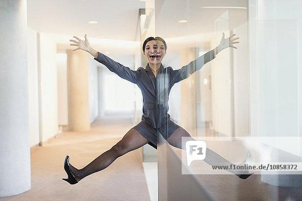 Symmetrisches Reflexionsporträt einer verspielten Geschäftsfrau mit Armen und Beinen im Büroflur