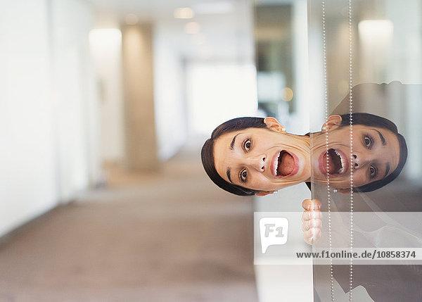 Reflexionsporträt einer überschwänglichen Frau beim Blick in den Büroflur