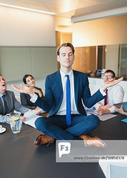 Kollegen beobachten zen-ähnliche Geschäftsleute  die in Lotusstellung auf dem Konferenztisch meditieren.