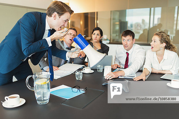 Schockierte Kollegen beobachten Geschäftsmann mit Megaphon schreien in Konferenz-Telefon