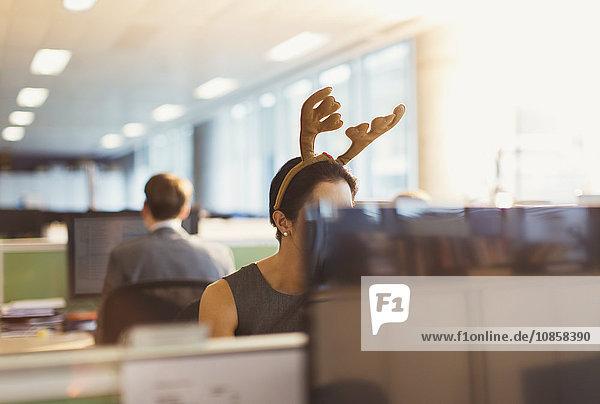 Geschäftsfrau mit Geweih-Stirnband im Büro