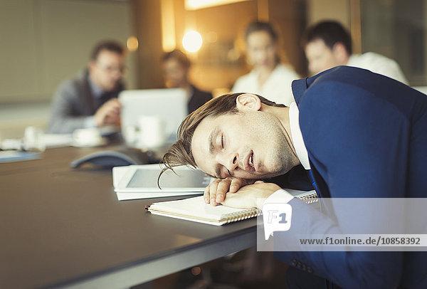 Geschäftsmann schläft in Konferenzraumbesprechung