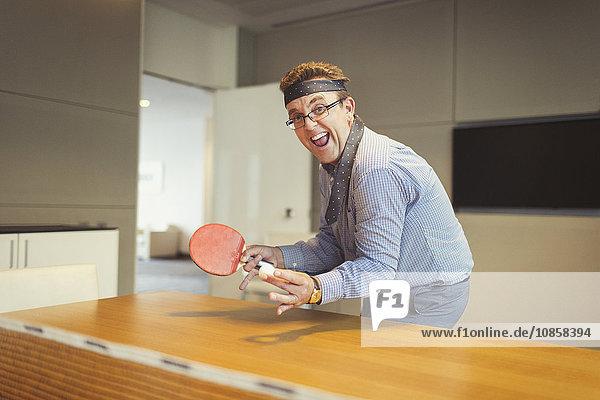 Porträt eines begeisterten Geschäftsmannes  der Tischtennis mit Krawatte um den Kopf im Konferenzraum spielt.