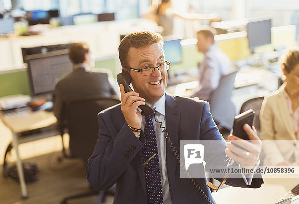 Verspielter Geschäftsmann  der am Telefon spricht und Selfie im Büro nimmt.