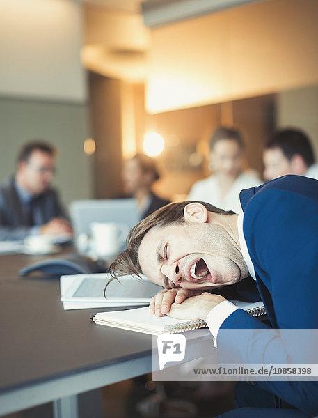 Müde Geschäftsleute gähnen und auf dem Konferenztisch liegend