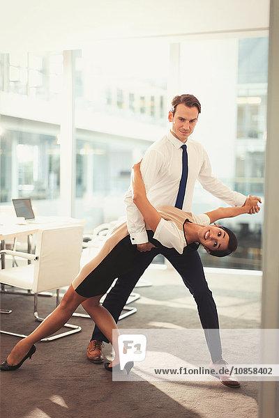 Portrait eines Geschäftsmannes und einer Geschäftsfrau beim Tangotanzen im Konferenzraum