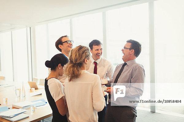 Lachende Geschäftsleute genießen Kaffeepause im Konferenzraum